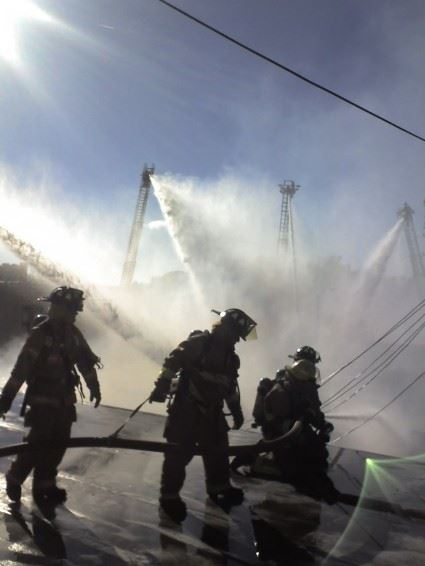Fire fighters working with water hoses