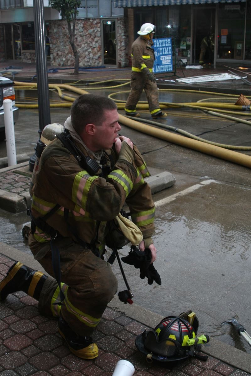 Fire fighter on a knee adjusting his gear
