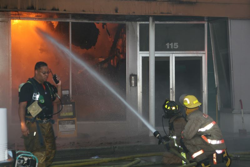 One fire fighter on the walkie talkie while two others spray a fire inside a building