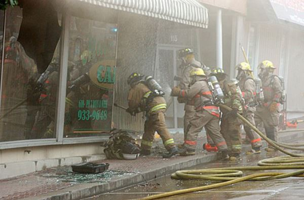 Group of fire fighters spraying a building through the windows