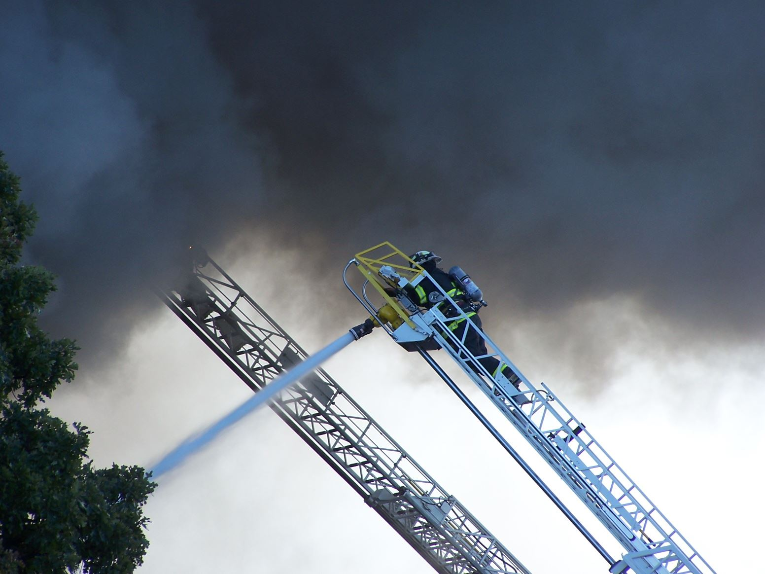 Fire fighter on a ladder spraying a fire