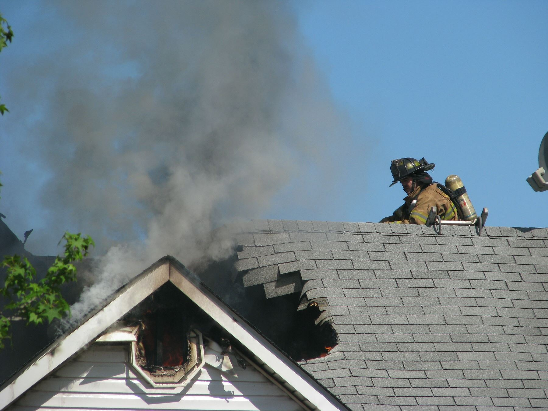 Fire fighters on top of a house that was on fire