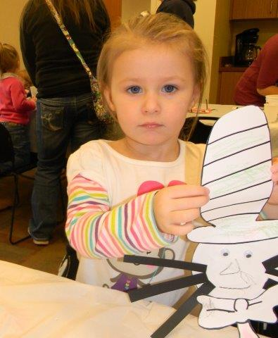 Young girl showing the camera her Cat in the Hat craft