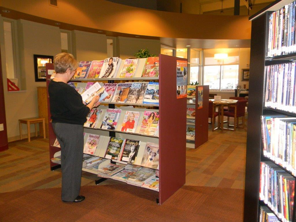 Woman reading a magazine by the magazine rack