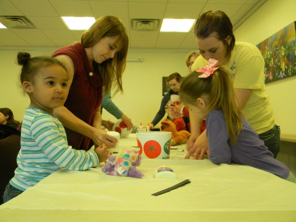Adults helping small children create crafts